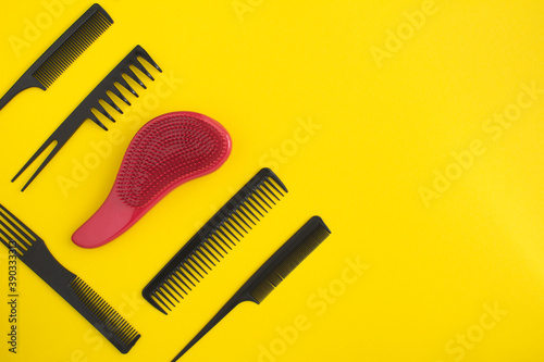 Top view of black and red hair combs on the yellow background with copy space Canvas