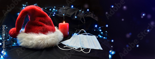 Fototapeta face masks put on next to a red santa claus hat and a candle in blur lights background obraz