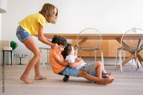 Cheerful children playing with skateboard at home. Blonde adorable girl pushing her two playful brothers. Happy kids riding on board and having fun. Childhood, game activity and weekend concept