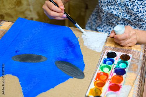 a girl drawing blue gouache cardboard, artistic creation at home, makes creative Canvas Print