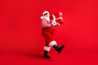 Full length photo of grandfather grey beard step hold big box white bow wear santa claus x-mas costume suspenders sunglass striped shirt cap boots isolated red color background