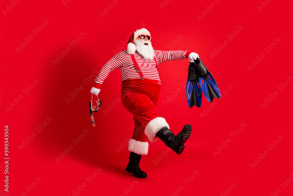 Fototapeta Full length profile photo of grandfather grey beard walk hold mask fins wear santa claus x-mas costume suspenders sunglass striped shirt hat boots isolated red color background