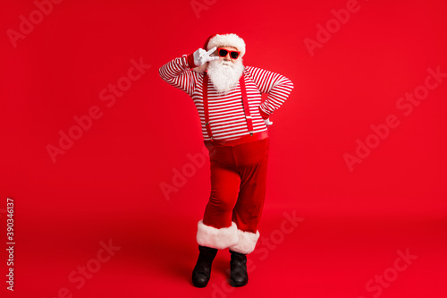 Obraz Full length body size view of his he nice handsome cheery comic childish flirty Santa father having fun celebratory festal day showing v-sign isolated bright vivid shine vibrant red color background - fototapety do salonu