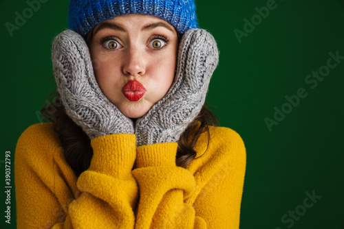Nice amusing girl in knit hat and mittens grimacing at camera Canvas Print