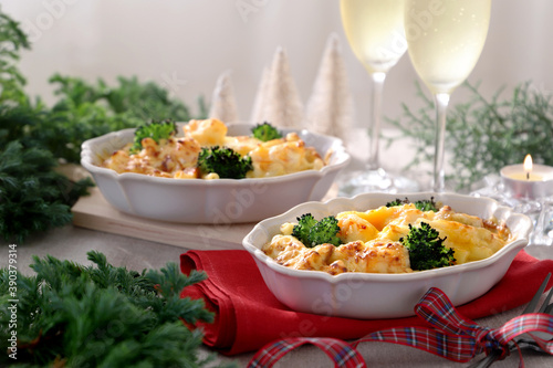 Homemade gratin with shrimp and cheese in baking dishes on Christmas decoration table Billede på lærred