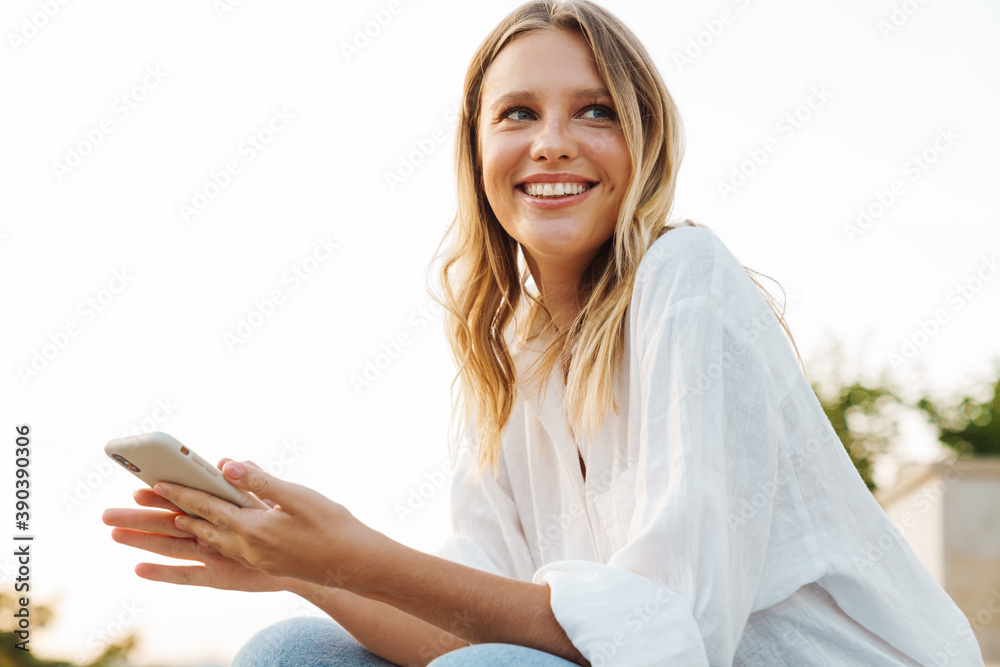 Fototapeta Nice happy woman smiling and using mobile phone while sitting outdoors