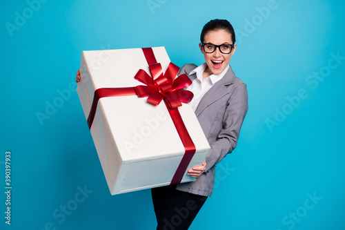 Corporate party concept celebrate anniversary. Shocked positive girl agent broker get receive big huge dream package gift box wear grey blazer jacket isolated blue color background