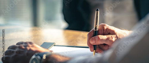 Obraz na plátne Closeup Businessman signing a contract investment professional document agreement on the table with pen