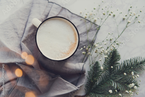 Fotografia Cup of cappuccino with gypsophila flowers warm lights bokeh top view