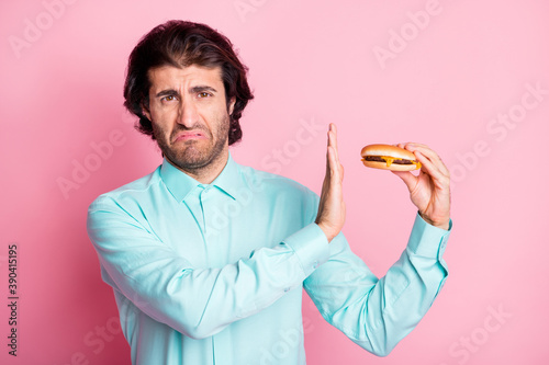 Photo Photo portrait of man disgusted holding cheeseburger in hand refusing with palm