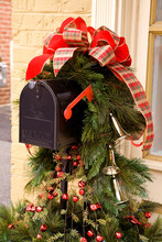 Christmas Holiday  Mailbox Decorated With A Large Red Bow, Ornaments, And Greenery
