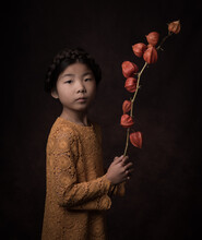 Studio Portrait Of Young Girl Holding A Branch Of  An Orange Lantern Flower, In Rembrandt Style (Cape Gooseberry, Physalis Alkekengi )