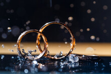 Gold Wedding Rings For Newlyweds On A Wedding Day On A Black Background With Water Drops. Jewelry