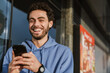 Happy handsome guy smiling and using mobile phone