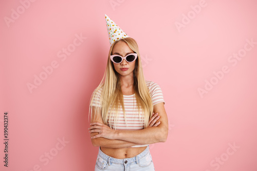 Obraz Caucasian beautiful girl in party cone posing with arms crossed - fototapety do salonu