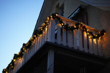 Christmas Wreaths With Candle Lights On Wooden Balcony In The Dusk At Christmastime. Tree At Left Side With Space In The Middle. Low Angle View.