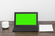 A Tablet With A Green Screen On A Wooden Table, A White Cup And Notepad Stands Near.