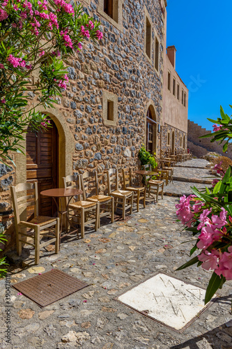 Fototapety, obrazy: Traditional cafe exterior in the fortified medieval  castle of Monemvasia. Iron tables and wooden chairs with the view of the  aegean sea in the background.