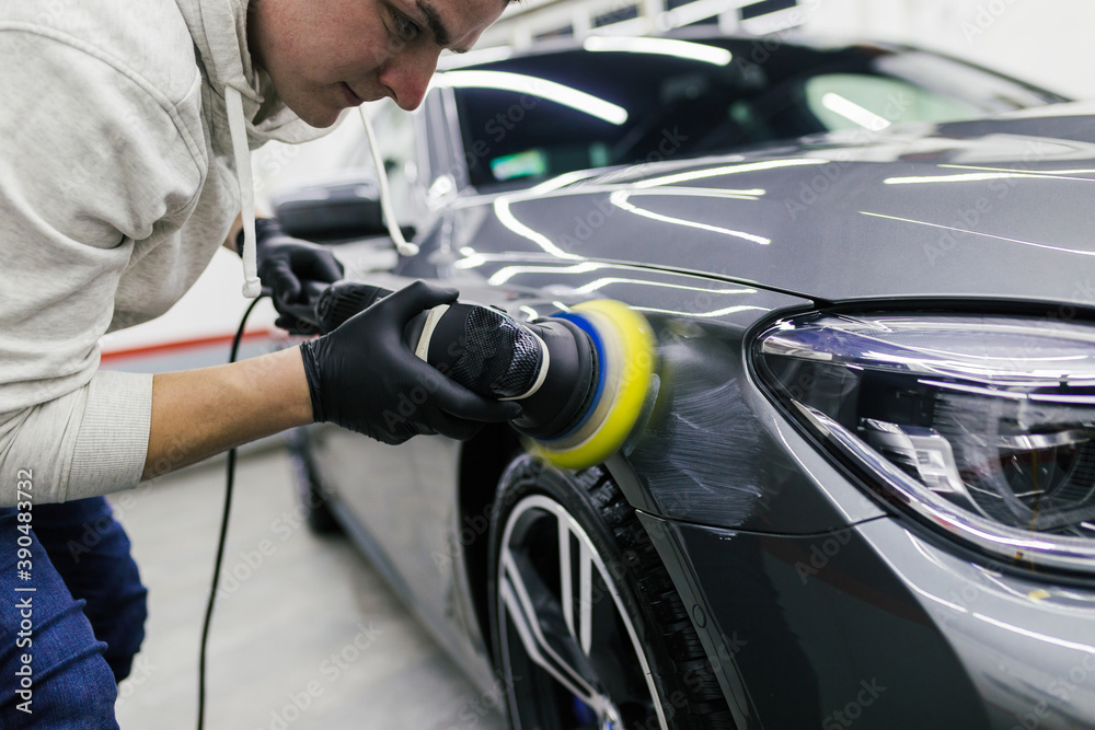 Fototapeta Car detailing - Worker with orbital polisher in auto repair shop.
