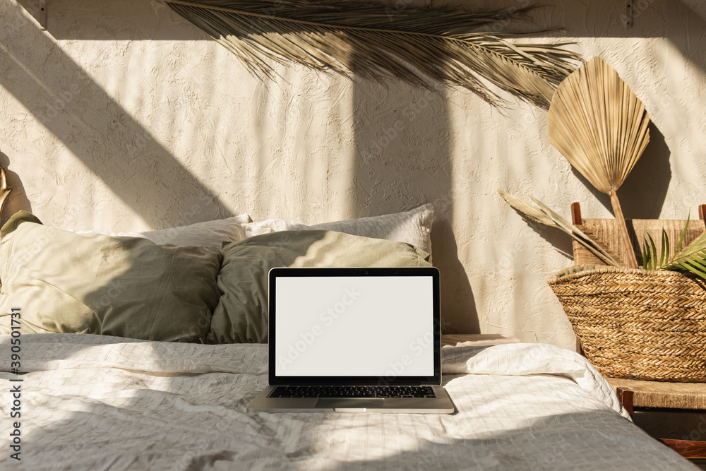 Fototapeta Blank screen laptop in bed with pillows and linens. Boho style home interior design with warm sunlight shadows on the wall. Copy space mockup template. Freelancer, blogger work business concept.