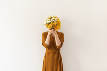 Young Beautiful Woman In Brown Dress Holding Bouquet Of Wildflowers Against White Wall. Minimal Beauty, Fashion Concept.