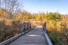 A Wooden Boardwalk Crosses A Marsh