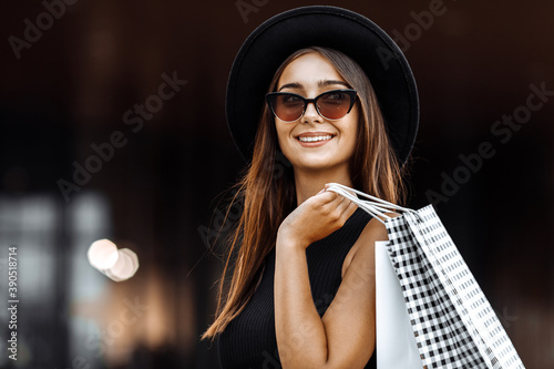 Foto attractive young woman in a black dress and hat, dark glasses, holding shopping bags, enjoying a successful shopping, in the background of the shopping center