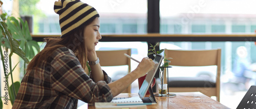 Slika na platnu Female teenager working with digital tablet on wooden table