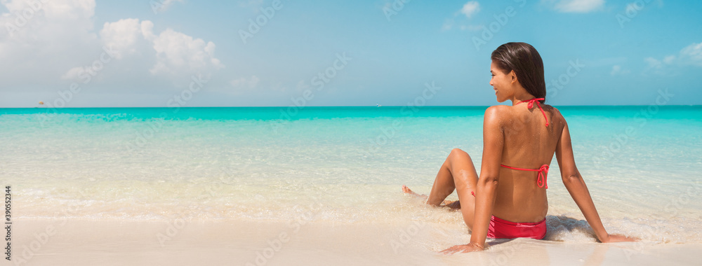 Fototapeta Beach vacation banner panorama background of bikini woman relaxing in water sun tanning on Caribbean island. Winter south holidays.