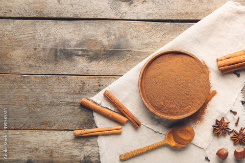 Cuadros en Lienzo Bowl and spoon with cinnamon powder on wooden background