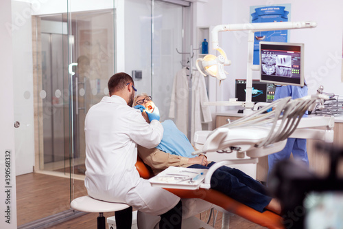 Fototapety, obrazy: Dentist examining senior patient mouth using angled mirror and scaler during treatment. Elderly patient during medical examination with dentist in dental office with orange equipment.