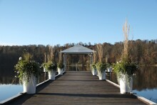 A Wooden Pier With White Gazebo And Flower Pots With Plants Over A Lake Surrounded By Forest In Autumn Scenery.