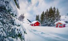 Traditional Norwegian Red Wooden Houses Under The Fresh Snow. Impressive Winter Scene Of Lofoten Islands On The Shore Of Kongsjordpollen Fjord, Vestvagoy, Norway, Europe. Life Over Polar Circle.