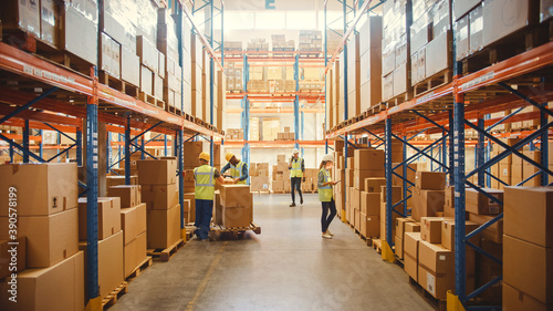 Fényképezés Retail Warehouse full of Shelves with Goods in Cardboard Boxes, Workers Scan and Sort Packages, Move Inventory with Pallet Trucks and Forklifts