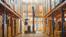 Retail Warehouse Full Of Shelves With Goods: Electric Forklift Truck Operator Lifted Pallet With Cardboard Box On A Shelf. Working In Logistics Storehouse Product Logistics And Delivery Center