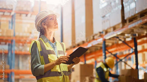 Professional Female Worker Wearing Hard Hat Checks Stock and Inventory with Digital Tablet Computer in the Retail Warehouse full of Shelves with Goods Fototapet