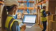 Professional Female Worker Wearing Hard Hat Holds Laptop Computer With Screen Showing Inventory Checking Software In The Retail Warehouse Full Of Shelves With Goods. Over The Shoulder Side View
