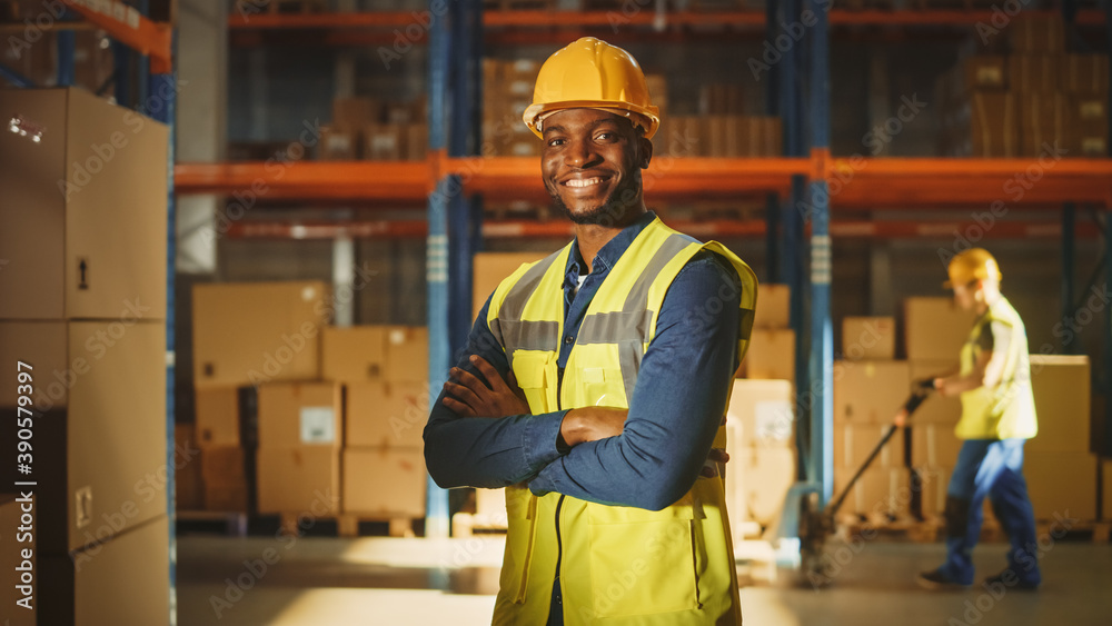 Leinwandbild Motiv - Gorodenkoff : Handsome and Happy Professional Worker Wearing Safety Vest and Hard Hat Smiling with Crossed Arms on Camera. In the Background Big Warehouse with Shelves full of Delivery Goods. Medium Portrait