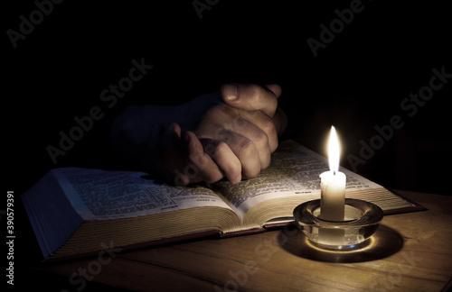 Fotografiet Hands folded in prayer over Scriptures
