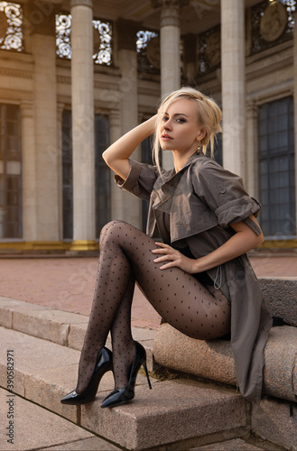 Obraz Beautiful blonde woman with perfect legs in pantyhose posing outdoor at the autumn street in the lights of the setting sun. - fototapety do salonu