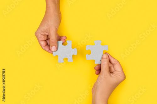 Fotografija Manos uniendo dos piezas de puzzle sobre un fondo amarillo liso y aislado