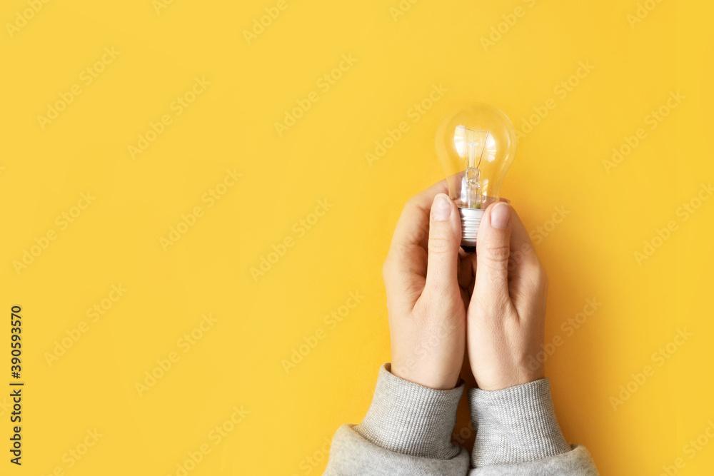 Fototapeta The emergence of a new creative idea. A glowing light bulb is a symbol of a brilliant idea