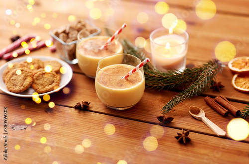 christmas and seasonal drinks concept - glasses of eggnog with oatmeal cookies, candy canes, sugar, fir tree branches and candle burning on wooden background over lights
