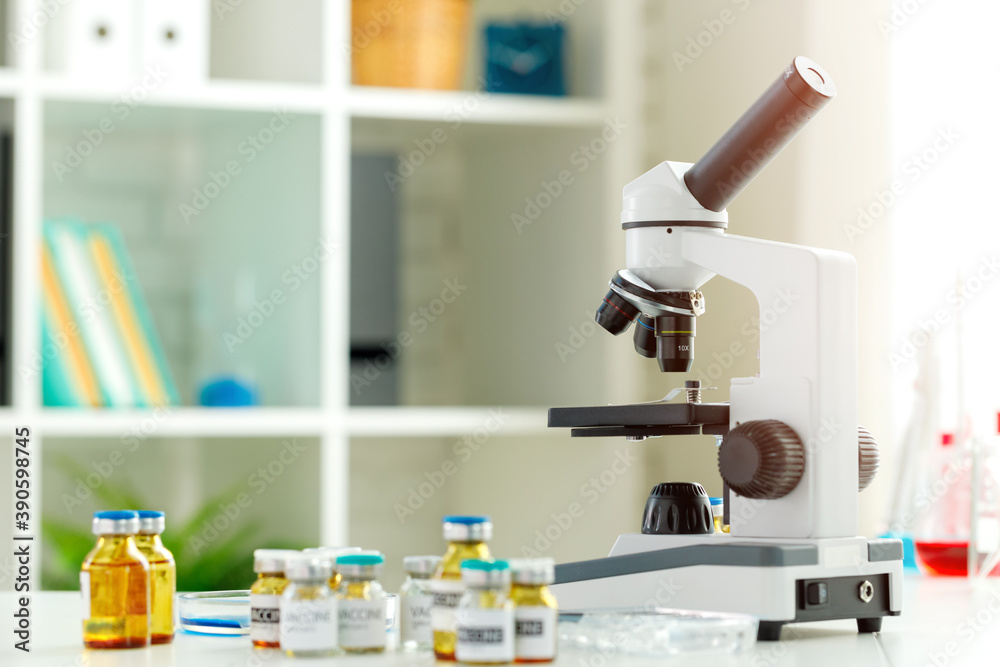 Fototapeta Vaccine bottles and microscope on table in a scientific lab
