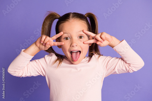 Photo of playful cute small child make face show v-sign funky mood isolated on purple color background