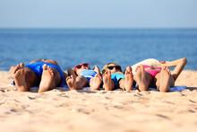Family Lying On Sandy Beach Ne...