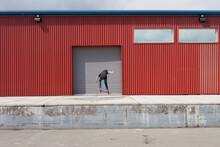 Teenage Boy Skateboarding In Front Of Industrial Warehouse Loading Zone