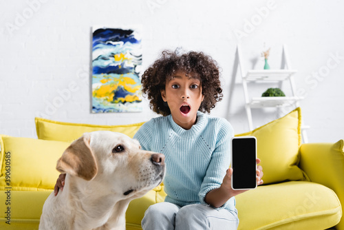 Canvastavla excited african american girl showing smartphone with blank screen and sitting n