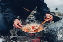 A Wild Camper Stirring Hot Food In A Pot Cooking Over A Fire.
