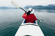 A Middle-aged Woman Paddles Sea Kayak In The Calm Waters Of Muir Inlet, Glacier Bay National Park And Preserve, Alaska